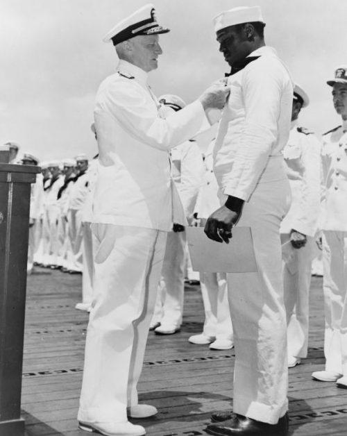 Адмирал Нимиц награждает Дориса Миллера Военно-морским крестом на борту авианосца «Энтерпрайз» за героические действия на борту линкора «Западная Вирджиния» во время атаки базы Перл Харбор японским авианосным соединением. Май 1942 г.