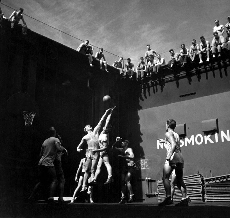Матросы легкого авианосца «Монтерей» и летчики морской авиации играют в баскетбол в шахте опущенного вниз переднего самолетоподъемника. Выпрыгивающий слева игрок - будущий 38-й президент США Джеральд Форд. Июль 1944 г.