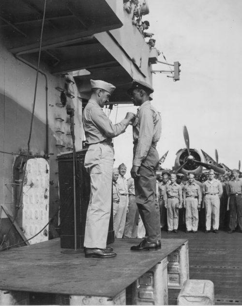 Капитан Х.У. Тейлор награждает матроса Фреда Мэги за храбрость при спасении моряка, упавшего за борт в море. Авианосец «Коупенс, октябрь 1944 г.