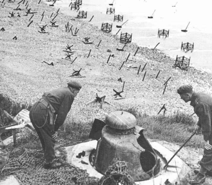 Канадские офицеры осматривают захваченный ДОТ на побережье.