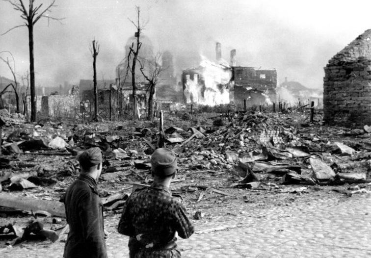 Военнослужащие войск СС на разрушенной улице города Нарва после налета советской авиации. 1944 г.