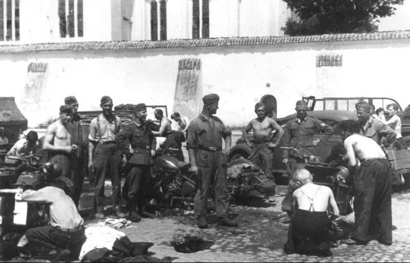 Евреи из Каунаса моют мотоциклы под надзором немецких солдат. 27 июня 1941 г.