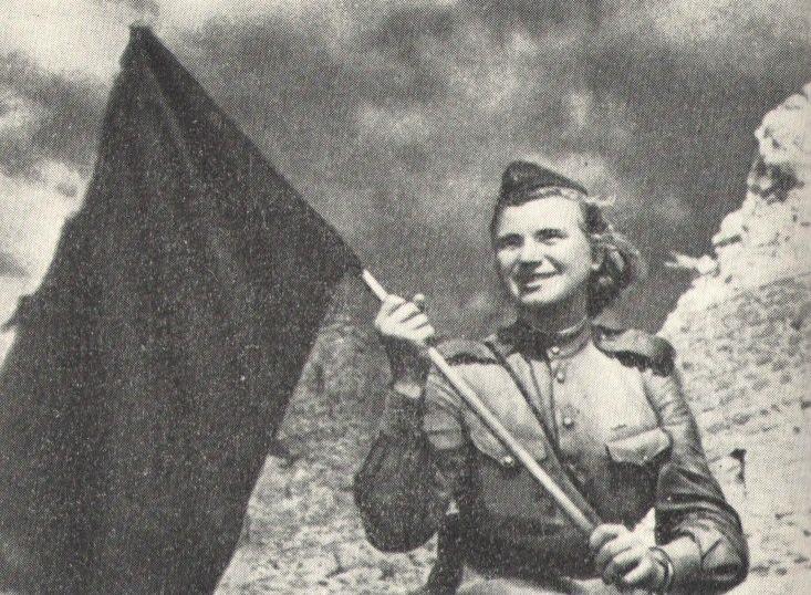 Пулемётчица В. Полежаева после штурма Нарвы водрузила на старой крепости советский флаг. Июль 1944 г.