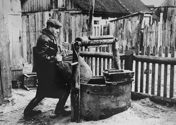 Член подполья Ковенского гетто прячет припасы в колодце. 1942 г.