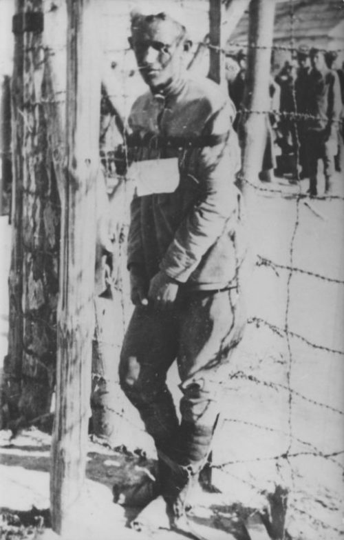 Советский военнопленный, привязанный к колючей проволоке в концлагере Майданек. 1942 г.