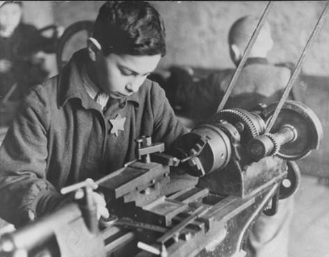 Подросток работает на станке на фабрике в гетто. 1943 г.