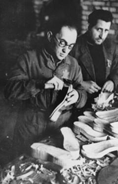 Еврейские подневольные рабочие шьют обувь в мастерской гетто. Декабрь 1943 г.