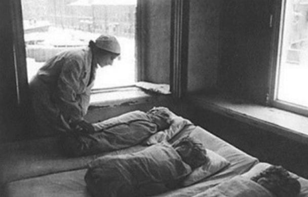 Медсестры укладывают новорожденных в кроватки. Ленинград, 1942 г.