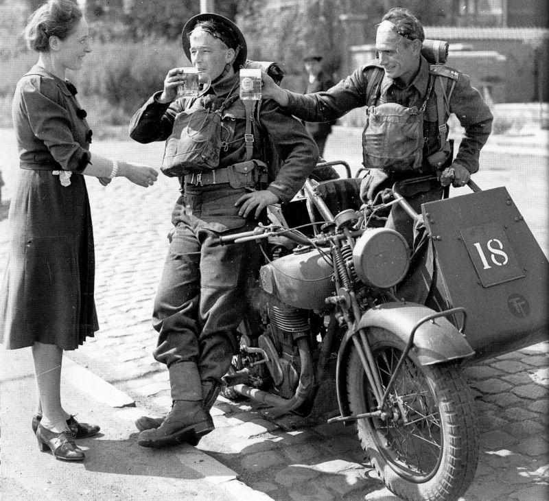 Жительница бельгийского городка угощает пивом солдат 50-й британской пехотной дивизии, выдвигающихся к линии фронта. Май 1940 г.