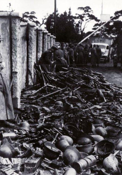 Эвакуируемые немецкие солдаты перед погрузкой на суда в Пиллау бросают свое оружие и снаряжение. Апрель 1945 г.