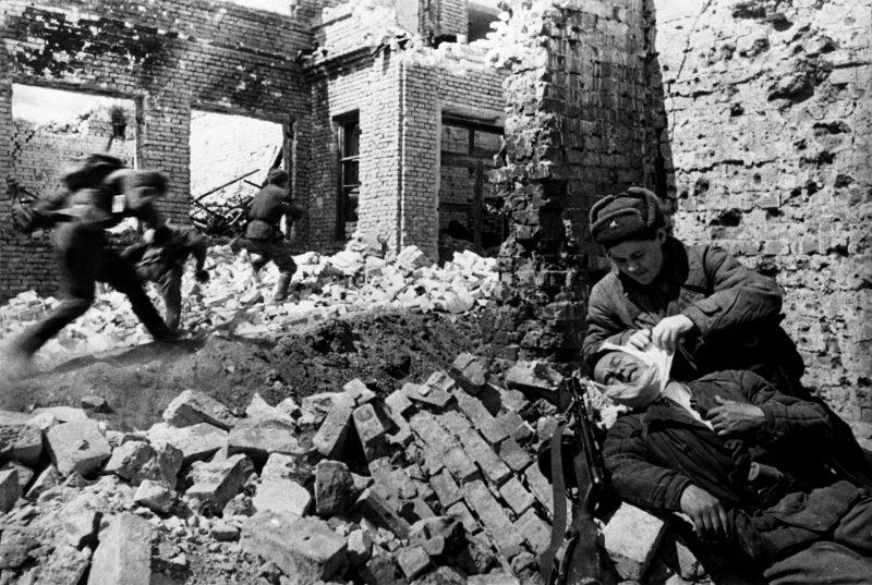 Санитарка перевязывает раненого во время уличного боя. Сталинград, декабрь 1942 г.