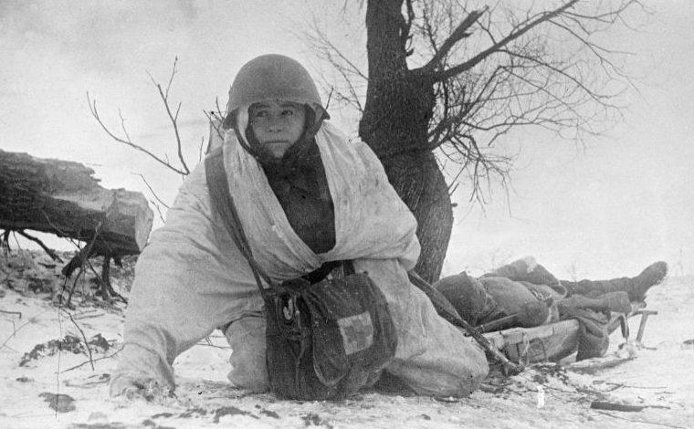 Санитар Людмила Пискунова вывозит на санях-носилках красноармейца, раненого на Западном фронте. Декабрь 1942 г.