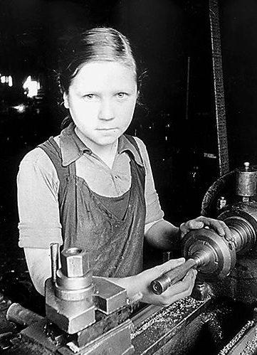 Токарь 3-го разряда пятнадцатилетняя Вера Тихова на ленинградском заводе. 1942 г.
