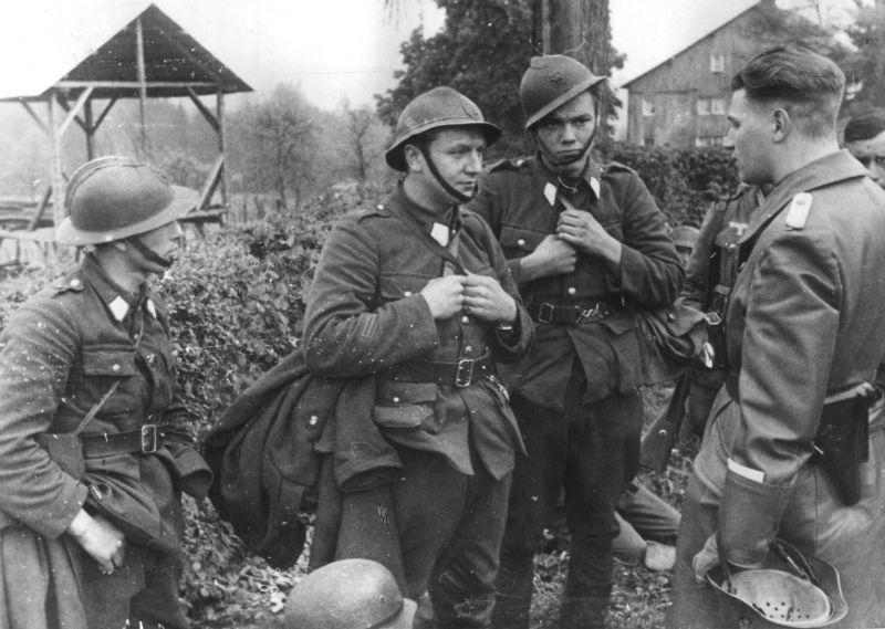 Немецкий офицер допрашивает пленных бельгийских солдат. Май 1940 г.