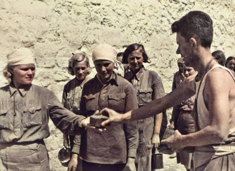 Немецкий солдат выдает хлеб советским девушкам в лагере военнопленных. 1942 г.