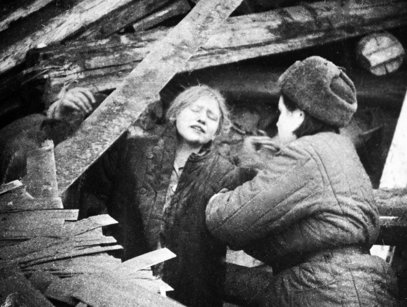 Медик помогает выбраться жительнице Ленинграда из-под обломков дома, разрушенного немецкой бомбардировкой. 1942 г.