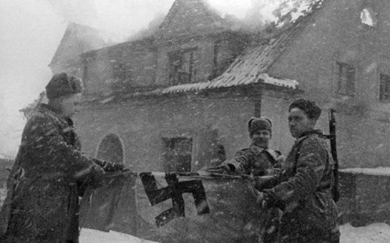 Уничтожение немецкого флага, захваченного в городе. Январь 1945 г.
