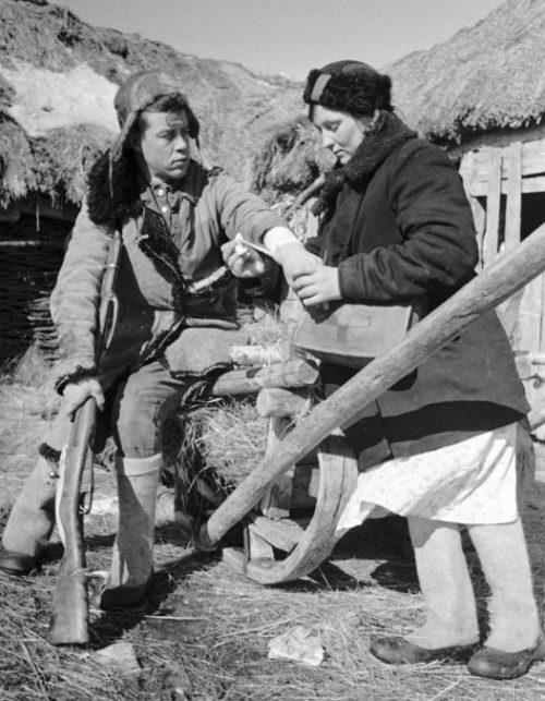 Медсестра партизанского отряда имени Фрунзе перевязывает руку бойцу отряда. 1942 г.