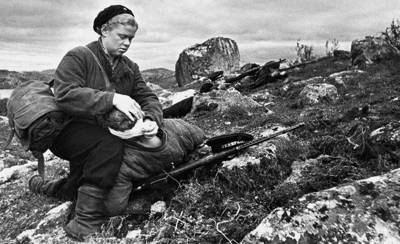 Санинструктор 125-го полка морской пехоты сержант Нина Буракова перевязывает раненого бойца в Заполярье. 1942 г.