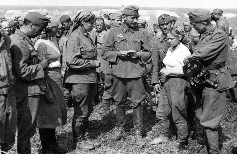 Венгерские корреспонденты и кинооператор разговаривают с женщинами-военнослужащими на сборном пункте советских военнопленных на Восточном фронте. 1942 г.