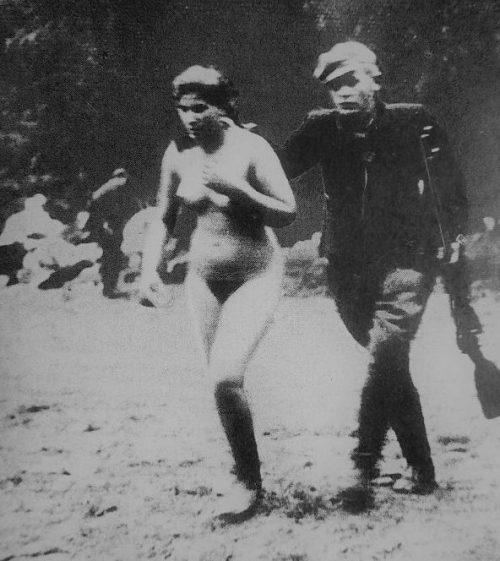 Сотрудник эстонской вспомогательной полиции ведет раздетую еврейку к месту расстрела. 1941 г.
