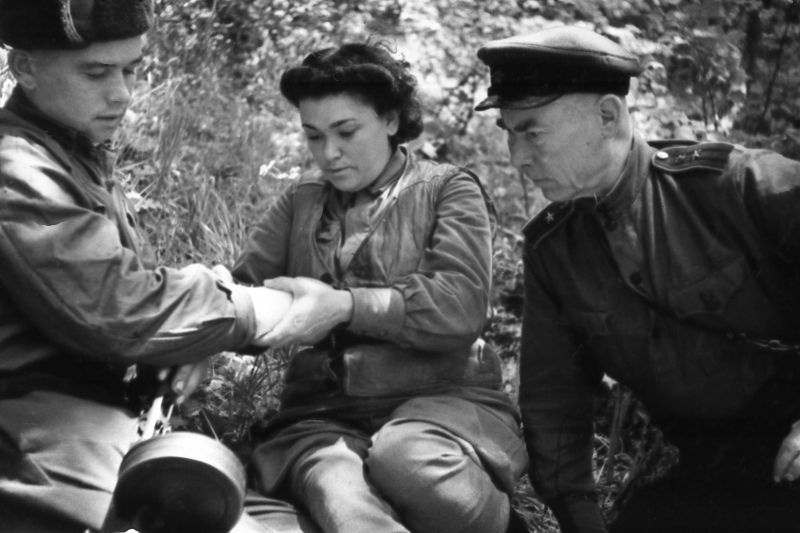 Медик разведгруппы «Соколы» Отдельной мотострелковой бригады особого назначения НКВД СССР перевязывает раненого в руку партизана. Август 1943 г.
