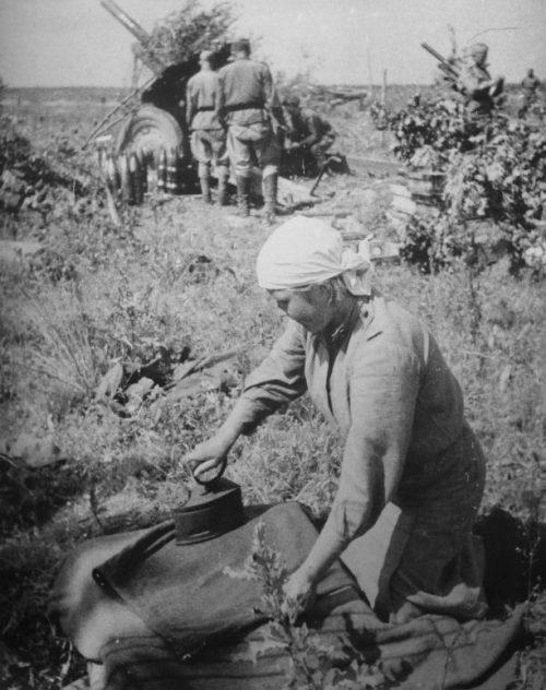 Военнослужащая гладит юбку рядом с позицией гаубиц М-30. 1943 г.