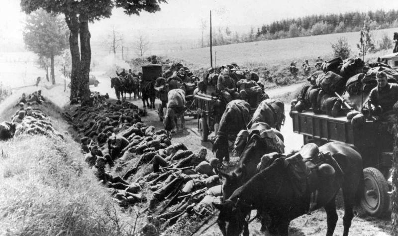 Отдыхающие в канаве немецкие солдаты и обоз на дороге в Бельгии. Май 1940 г.