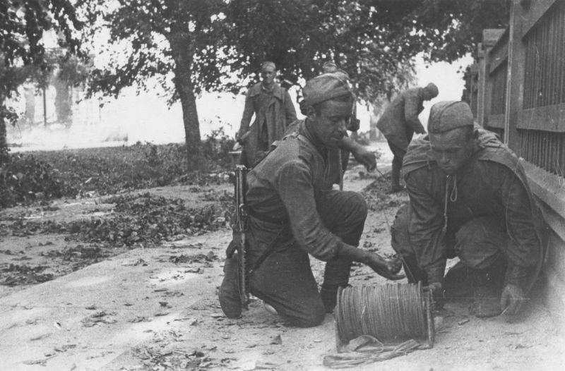 Советские связисты прокладывают линию связи во время уличных боев в Тарту. Август 1944 г.