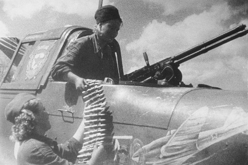 Девушки-оружейницы 7-го гвардейского штурмового авиаполка заряжают 12,7-мм авиационный пулемет УБТ. 1943 г.
