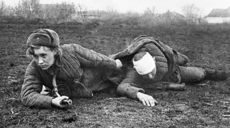 Санинструктор В. С. Грибкова эвакуирует раненого с поля боя. Февраль 1944 г.