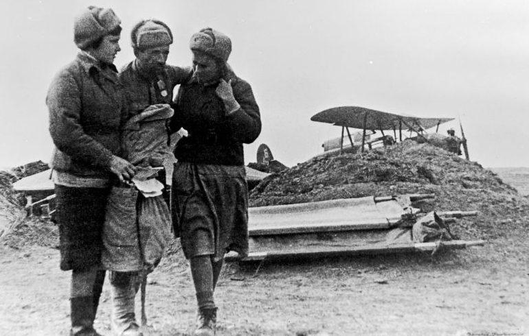 Санитарки ведут раненого красноармейца, доставленного через озеро Сиваш в тыл на самолете С-3. Апрель 1944 г.