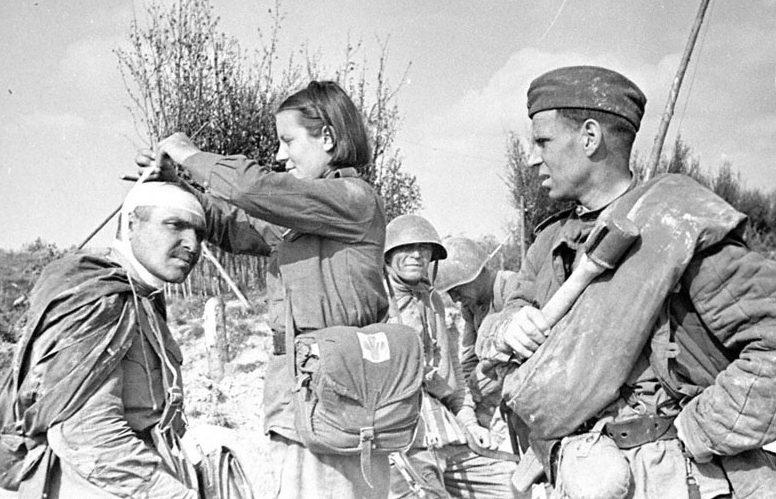 Санинструктор А.Н. Подчуфарова оказывает первую помощь раненому красноармейцу. Ленинградский фронт 1944 г.