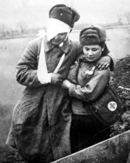 Санинструктор Матрёна Нечепорчукова оказывает помощь сержанту Рогачёву, раненому в ходе боев на Одере. Апрель 1945 г.