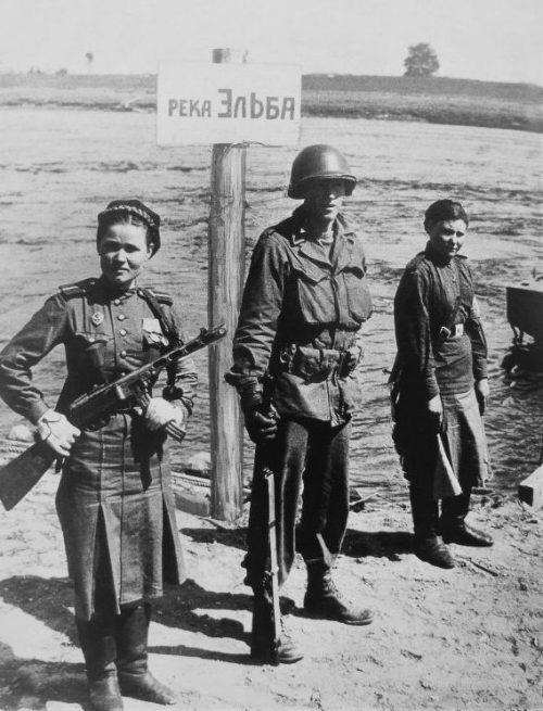 Девушки-военнослужащие Красной Армии и американский солдат на берегу Эльбы в городе Торгау. Май 1945 г.