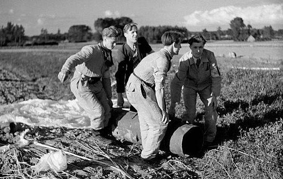Члены бельгийского подпольного сопротивления забирают контейнер с оружием и боеприпасами, сброшенными на парашюте с самолета Союзников. Сентябрь 1944 г.