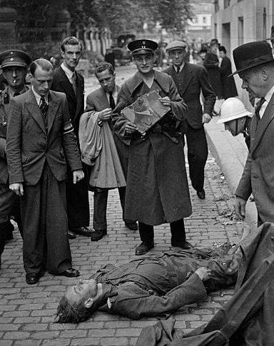 Члены бельгийского Сопротивления позируют у трупа немецкого солдата. Брюссель, сентябрь 1944 г.