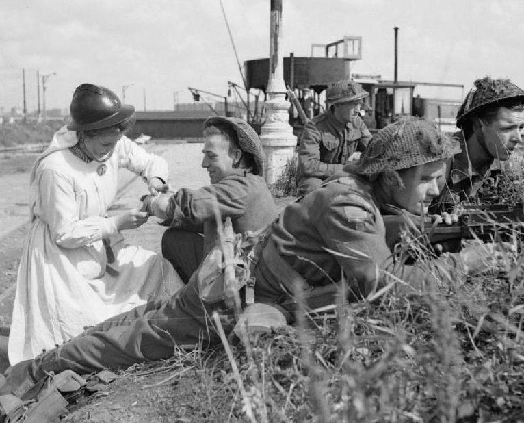 Медсестра Сопротивления оказывает первую помощь британскому солдату во время боев у Антверпена. Сентябрь 1944 г.
