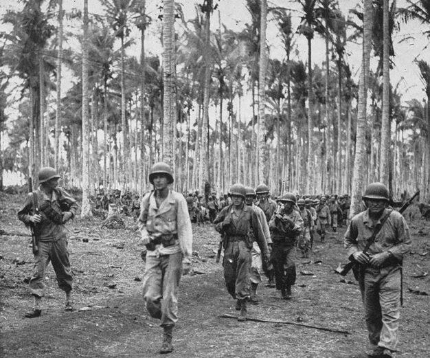Американские пехотинцы проходит через кокосовую плантацию Араве.