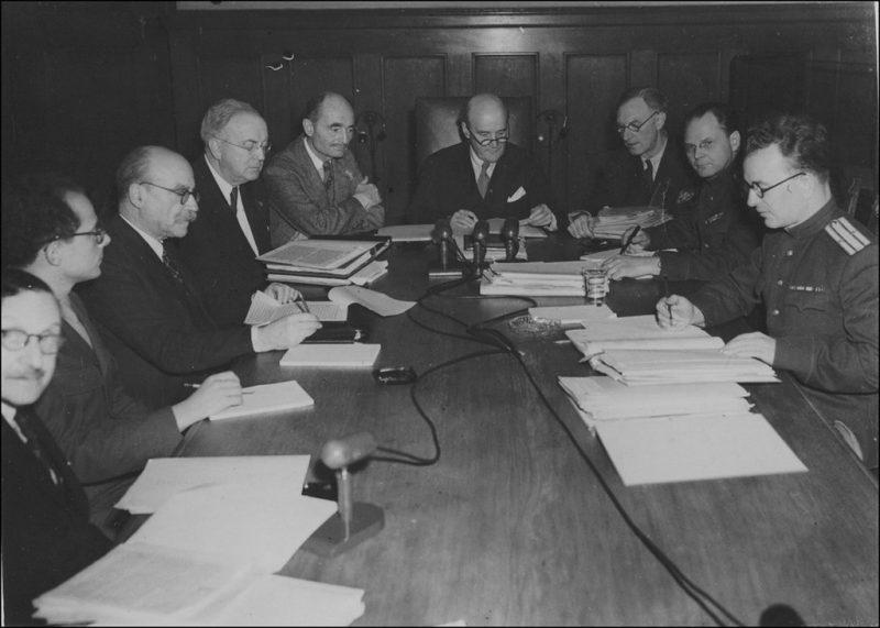 Судьи Нюрнбергского трибунала просматривают документы за столом в комнате для совещаний. 1945 г.