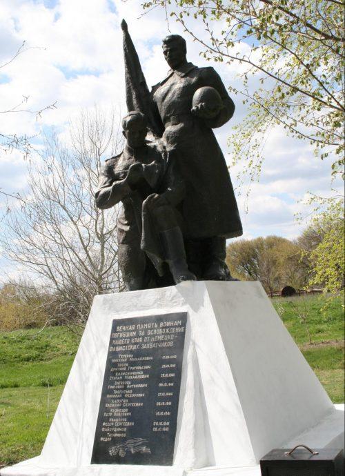 с. Дмитровка Бердянского р-на. Памятник у средней школы, установленный на братской могиле, в которой похоронено 12 советских воинов, в т.ч. 2 неизвестных.