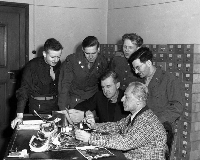 Личный фотограф А.Гитлера Г.Гофман разъясняет содержание своих фотографий представителям обвинения на Нюрнбергском процессе. 1945 г.