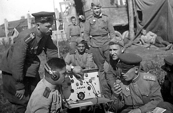 Красноармейцы и офицеры около полевой радиостанции. Август 1945 г.