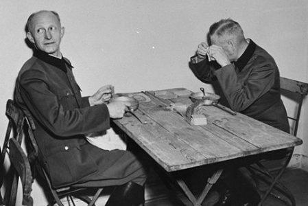 Обвиняемые Альфред Йодль (слева) и Вильгельм Кейтель (справа) обедают в импровизированной столовой, примыкающей к залу суда, на процессе Международного военного трибунала в Нюрнберге. 1945 г.
