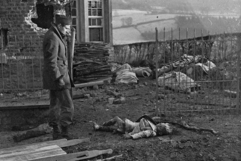 Военный корреспондент Жан Marin смотрит на тела мирных жителей в Бельгии.