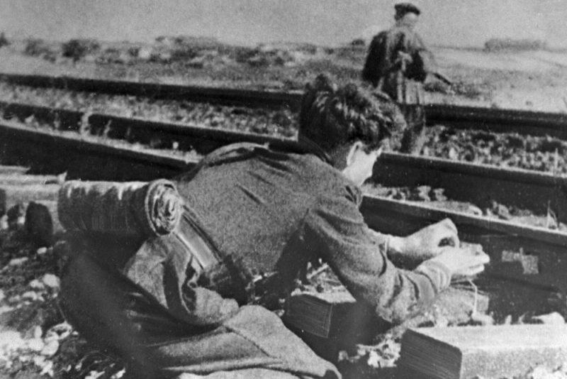Подрывники бригады «Народные мстители» закладывают взрывчатку под рельсы.