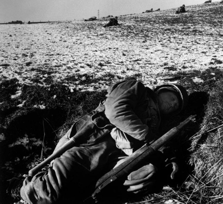 Американский солдат спит в поле в окрестностях Бастони. Декабрь 1944 г.