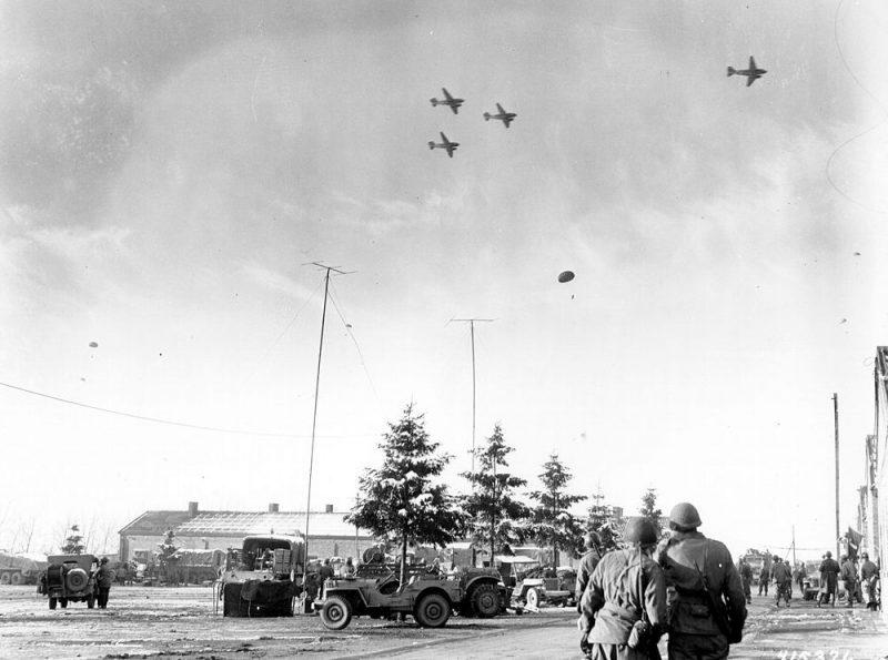 Солдаты 101-й воздушно-десантной дивизии наблюдают, как самолеты C-47 сбрасывают им припасы на поле недалеко Бастони. Декабрь 1944 г.