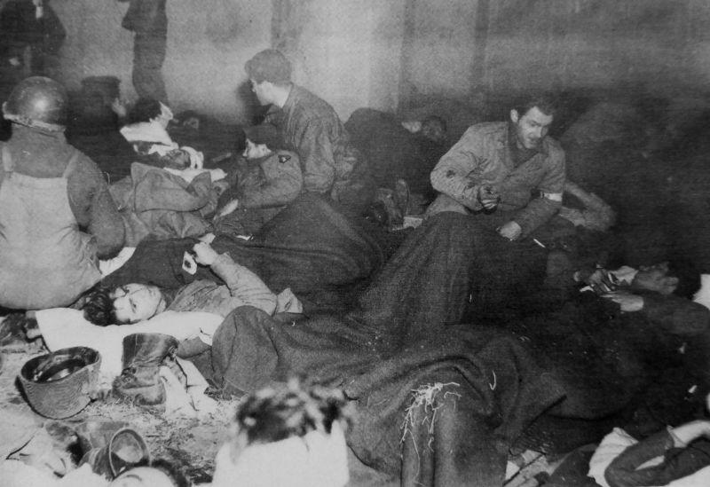 Раненые американские солдаты в подвале дома в осажденном немецкими войсками Бастони. Декабрь 1944 г.