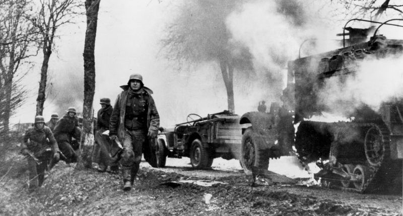 Солдаты 2-й танковой дивизии СС «Дас Райх» на фоне уничтоженной в районе города Мане американской автоколонны. Декабрь 1944 г.